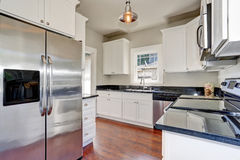 White kitchen room interior with granite counter top and hardwood floor. Stock Image