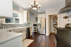 White kitchen room with stainless steel fridge and hardwood floor. stock image