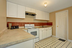 White kitchen room with tile floor and brown back splash tile. Stock Image
