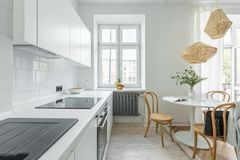 Kitchen with round table. White kitchen in scandinavian style with round table and wooden chairs stock image