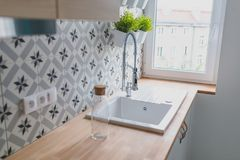 White kitchen sink with chrome faucet. Open bright kitchen with white furniture royalty free stock photo