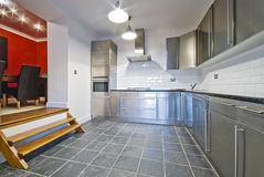 White kitchen with stainless steel cupboards. And granite worktop stock photo