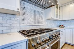White Kitchen with stainless steel hood over gas cooktop. White Kitchen with stainless steel hood over gas cooktop and carrera marble backsplash stock photo