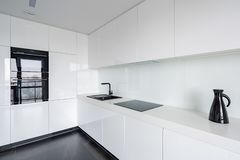 White kitchen with stone floor. White contemporary designed kitchen with stone floor and black accessories stock photo