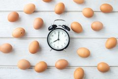 White kitchen table texture background with fresh eggs set and classic clock. View from top table royalty free stock photos