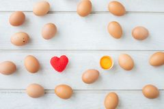 White kitchen table texture background with fresh eggs set , yellow yolk eggs and red heart shape sign. View from top table royalty free stock image