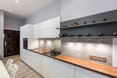 White kitchen with wooden countertop. Contemporary white kitchen with wooden countertop and led lighting stock photos