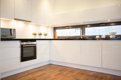 White kitchen with wooden floor royalty free stock photography