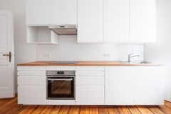 White kitchenette , newly built-in kitchen furniture frontal view with wooden worktop and board floor.  royalty free stock photos