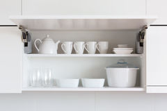 White kitchenware. Opened cupboar with kitchenware inside Stock Image