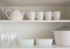 White kitchenware. Opened cupboard with kitchenware inside royalty free stock photography