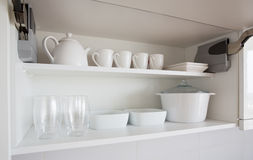 White kitchenware. Opened cupboard with kitchenware inside Royalty Free Stock Images