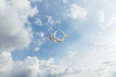 White kite flying against the blue sky full of clouds. Horizontal image royalty free stock images