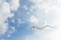 White kite flying against the blue sky full of clouds. Horizontal image royalty free stock photo