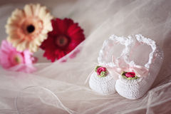 White knit baby booties decorated with flowers. And ribbons with gerberas in the background Royalty Free Stock Photos
