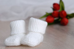 White knitted baby booties Stock Images