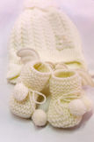 White knitted baby booties and hat Stock Images