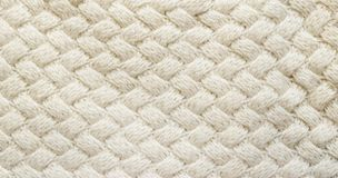 White knitted carpet closeup. Textile texture off white backgrou. Nd. Detailed warm yarn background. Knit cashmere beige wool. Natural woolen fabric, sweater Royalty Free Stock Photos
