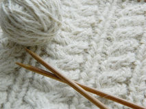 White knitted pattern. Ball of of yarn and knitting needles Stock Images