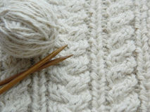 White knitted pattern. Ball of of yarn and knitting needles Royalty Free Stock Image