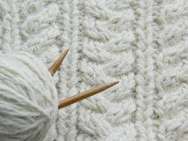 White knitted pattern. Ball of of yarn and knitting needles Royalty Free Stock Photos