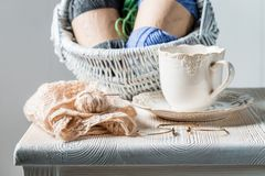 White knitted scarf with color skein and coffee. On white table Royalty Free Stock Images