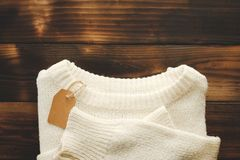 White knitted sweater with price tag on old wooden background top view. Fashion Lady Clothes Set Trendy Cozy Knit. Jumper Autumn accessories royalty free stock photography