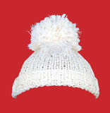 White knitted wool hat on red Stock Images