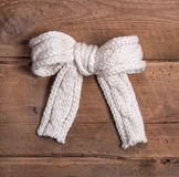 White knitted woolen bow on square wooden background Royalty Free Stock Photo