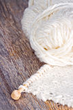 White knitting on rustic wooden background Stock Image
