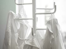 White lab dressings gown on a hanger. Moscow, Russia - September, 24, 2018: White lab dressings gown on a hanger in a class in Moscow privet school stock images