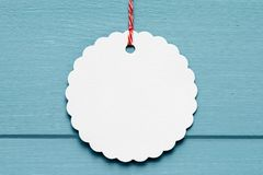 White label on blue background. A white label hanging from red and white string on a blue wood background stock image