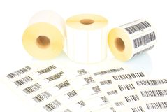 White label rolls and printed barcodes isolated on white background with shadow reflection. White reels of labels for printers. Labels for direct thermal or royalty free stock image