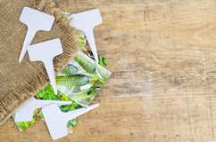 White labels-markers for plants lie on burlap, on wooden  background. Studio Photo royalty free stock image