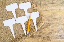 White labels-markers for plants lie on burlap, on wooden  background. Studio Photo stock photography