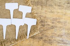 White labels-markers for plants lie on burlap, on wooden  background. Studio Photo royalty free stock images