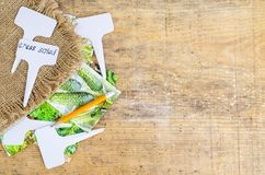 White labels-markers for plants lie on burlap, on wooden  background. Studio Photo stock images