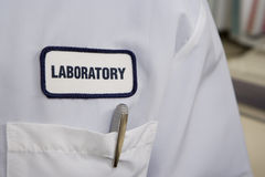 White laboratory coat, focus on label, pocket and pen, mid-section, close-up Stock Photo