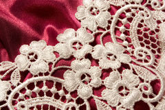 White lace. On a purple satin royalty free stock image