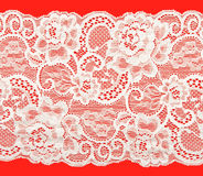 White lace. With a floral pattern on a red background Stock Photos