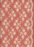 White lace with border on red background. A white/cream lace with border on a red background Royalty Free Stock Images