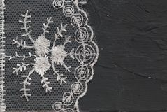 White Lace on Dark Surface Frame. Lace Texture Background on Dark Gray Textured Board with copy space. stock image