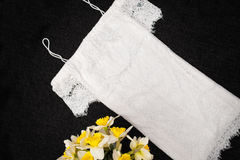 White lace dress and bouquet of daffodils. Black background. Fashionable concept Royalty Free Stock Photo