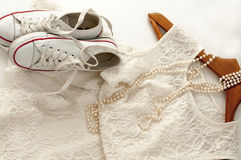 A white lace dress, a pair of sneakers on a wooden clothes hanger and a pearl necklace  on white Stock Images