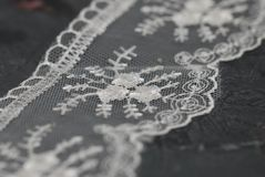 White Lace Embroidered Border on Dark Surface. Lace Texture Background on Dark Gray Board. White Lace Embroidered Border on Dark Surface. Lace Texture stock photos