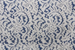 White lace fabric with floral pattern on blue Royalty Free Stock Image