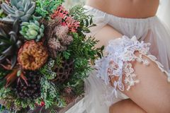 White lace garter on the leg. Bridal  leg in a white  lace garter and the colorful wedding bouquet near it Royalty Free Stock Photo
