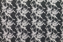 White lace over black background. Thin white lace with a beautiful pattern on a black background Stock Image