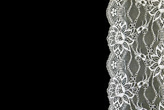 White lace over black background. Thin white lace with a beautiful pattern on a black background Stock Photography