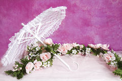 White Lace Parasol and Garland of Pink roses. A white lace parasol intertwined with pink tulle and a rose garland Royalty Free Stock Image